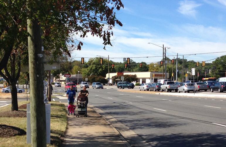 People walking on sidewalk next to highway