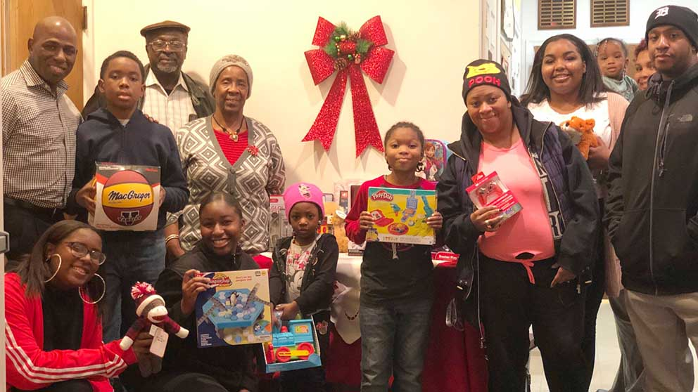 Children holding toys surrounded by church members.