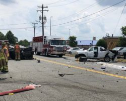 Crash scene with debris on road and two of the damaged vehicles