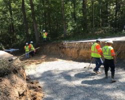 Four workers stand inside hole cut in road