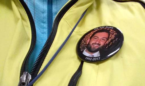 Person in yellow jacket wearing a We Are Bijan pin with his picture on it