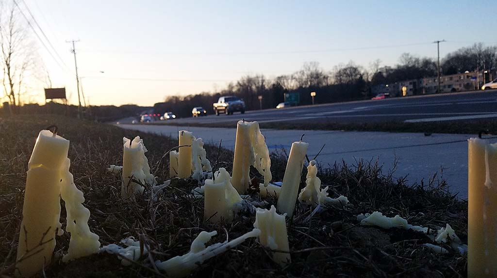 Candles half burned next to road