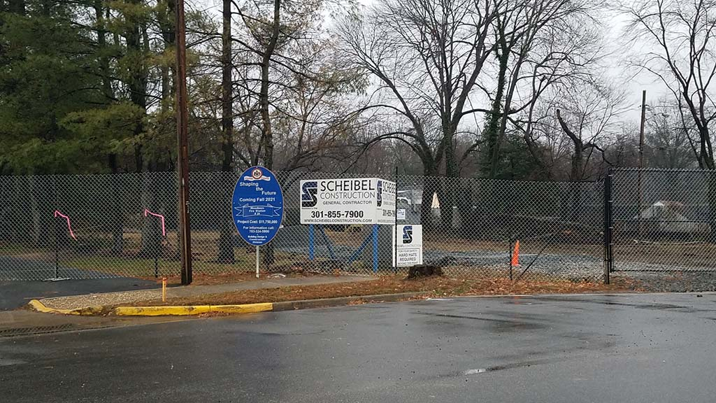 Scheibel Construction sign in front of site, which has temporary fence around it
