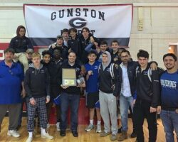 Coaches and team together in front of Gunston District banner