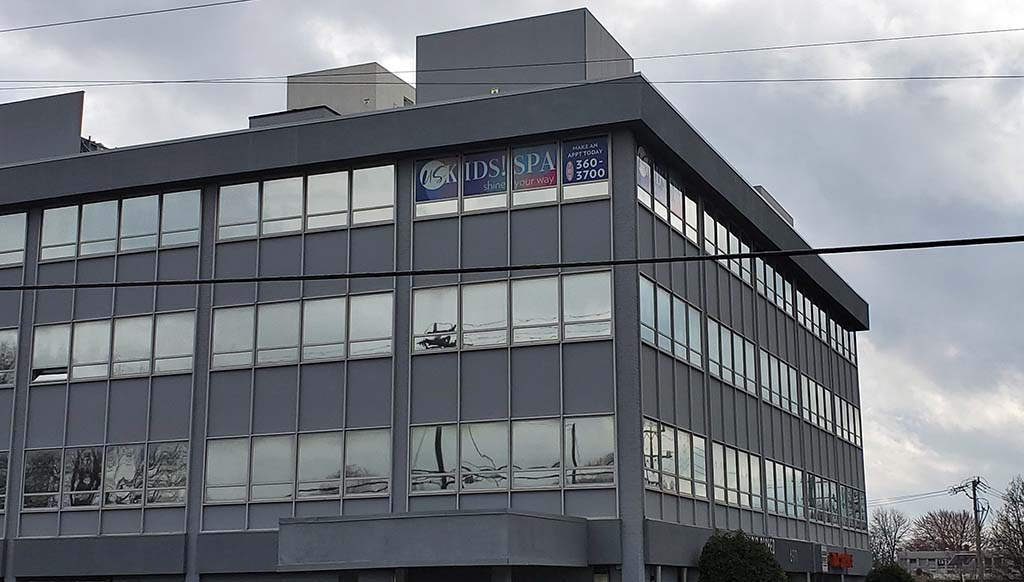 Office building on cloudy day with sign visible on top floor