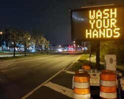 "A ""Wash Your Hands"" electronic billboard on the side of the road"