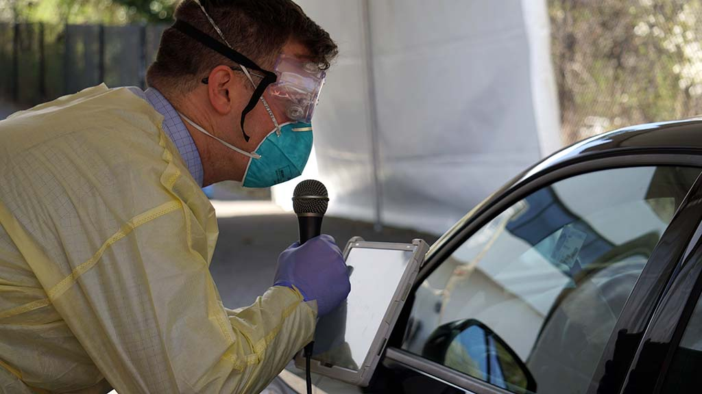 Medical worker holding a microphone and talking to person in car