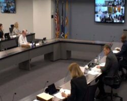 McKay and others sitting a few feet from each other and looking at other supervisors on screen